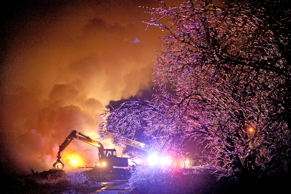 Staff photo by Michael G. Seamans CHRISTMAS FIRE: Waterville firefighters use an excavator mop up a major fire that destroyed a local business on Drummond Avenue in Waterville on Wednesday, Dec. 25, 2013.