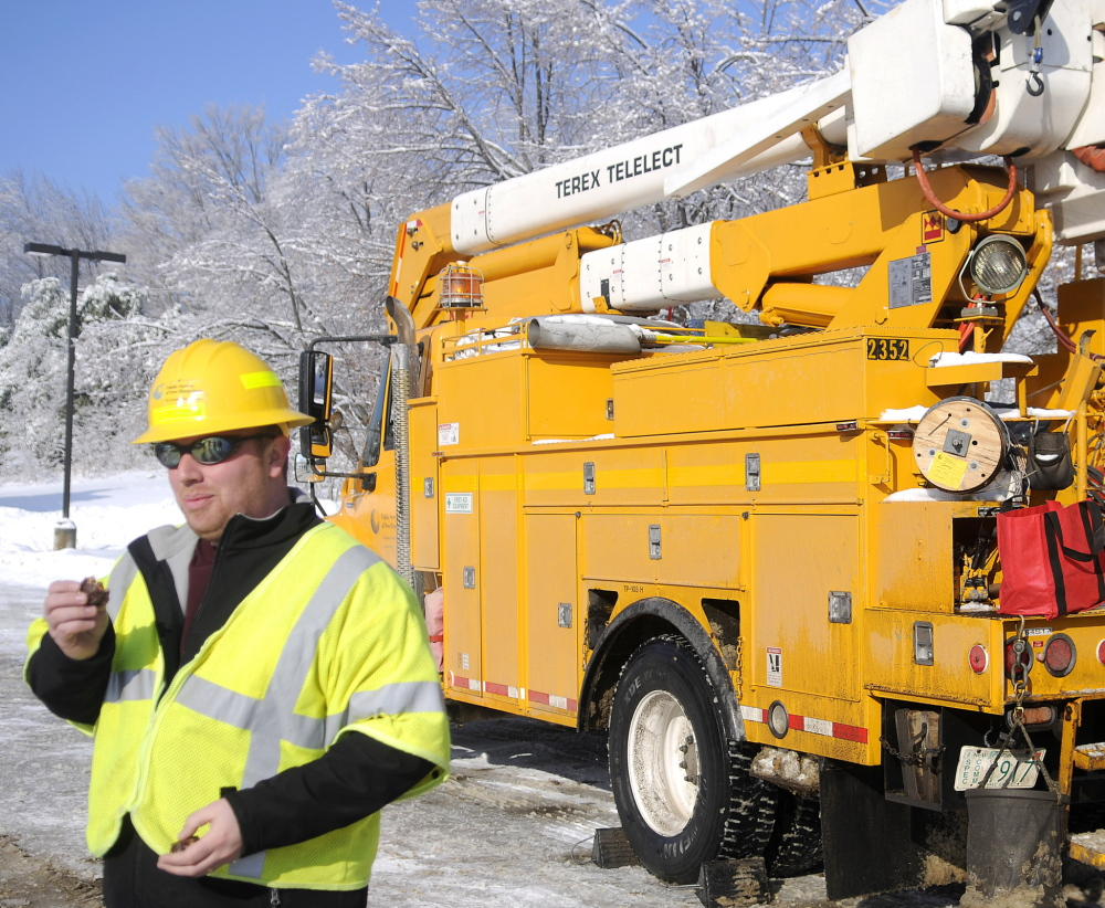 Public Service of New Hampshire line supervisor Chris Piccolo eats a cookie presented to his utility crew by a customer Friday while restoring power in Vassalboro. Several hundred out-of-state power and tree workers arrived in Kennebec County to restore power this week, often working 17 hour days in freezing temperatures. Crews in Vassalboro received tins of fudge, chocolate and boxes of peanut butter cookies from a resident grateful to be re-attached to the grid.