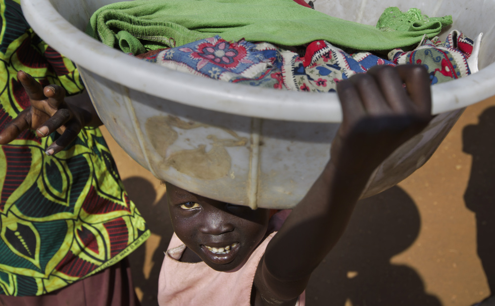 """A young displaced girl carries a basket of laundry inside a United Nations compound which has become home to thousands of people displaced by the recent fighting, in Juba, South Sudan Friday, Dec. 27, 2013. Kenya's president Uhuru Kenyatta on Friday urged South Sudan's leaders to resolve their political differences peacefully and to stop the violence that has displaced more than 120,000 people in the world's newest country, citing the example of the late Nelson Mandela and saying there is """"a very small window of opportunity to secure peace"""" in the country where fighting since Dec. 15 has raised fears of full-blown civil war."""