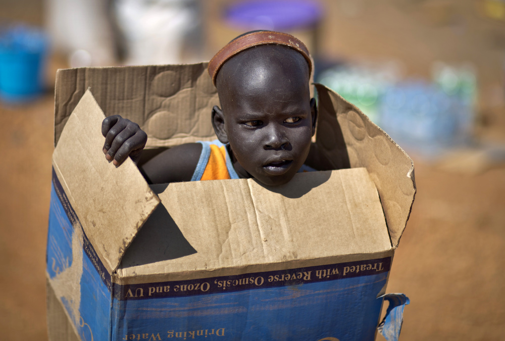 """A displaced boy carries a cardboard box inside a United Nations compound which has become home to thousands of people displaced by the recent fighting, in Juba, South Sudan Friday, Dec. 27, 2013. Kenya's president Uhuru Kenyatta on Friday urged South Sudan's leaders to resolve their political differences peacefully and to stop the violence that has displaced more than 120,000 people in the world's newest country, citing the example of the late Nelson Mandela and saying there is """"a very small window of opportunity to secure peace"""" in the country where fighting since Dec. 15 has raised fears of full-blown civil war."""