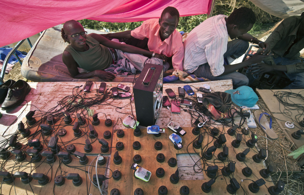"""Displaced men run a mobile phone charging station enabling others to keep in contact with relatives, inside a United Nations compound which has become home to thousands of people displaced by the recent fighting, in Juba, South Sudan Friday, Dec. 27, 2013. Kenya's president Uhuru Kenyatta on Friday urged South Sudan's leaders to resolve their political differences peacefully and to stop the violence that has displaced more than 120,000 people in the world's newest country, citing the example of the late Nelson Mandela and saying there is """"a very small window of opportunity to secure peace"""" in the country where fighting since Dec. 15 has raised fears of full-blown civil war."""