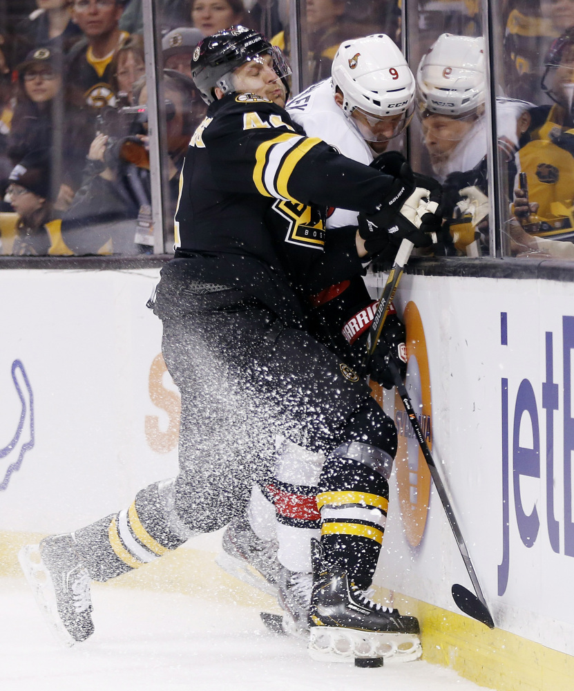 Boston Bruins' Dennis Seidenberg (44) checks Ottawa Senators' Milan Michalek (9) in the first period Friday.