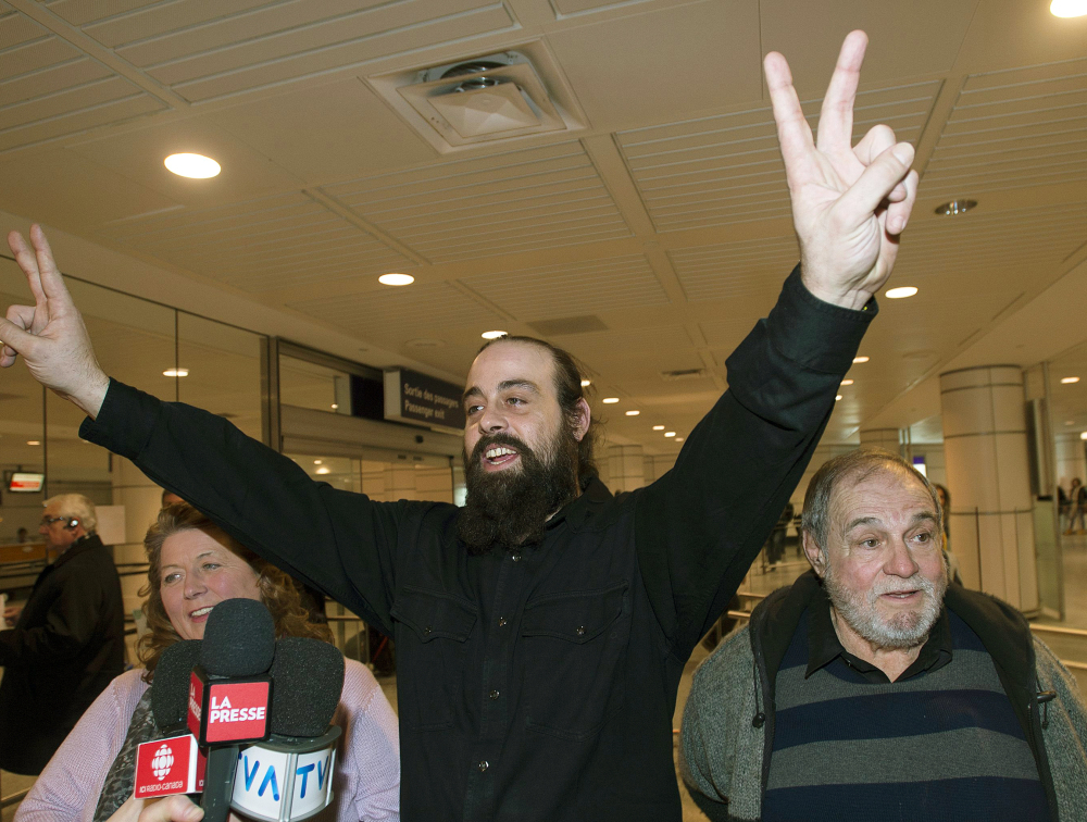 Greenpeace activist Canadian Alexandre Paul, flanked by his parents Nicole and Raymond in Montreal, signals victory.