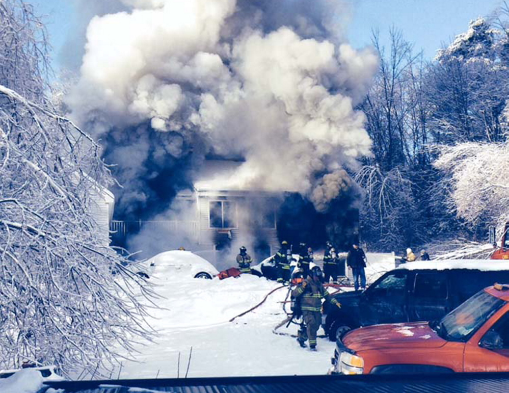 Firefighters battle a house fire Friday on Fire Road 14 on China Lake. One resident, who has cerebral palsy, was hospitalized for smoke inhalation and three dogs died.