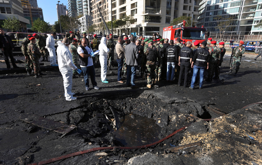 Lebanese army investigators in white coveralls stand at the scene of an explosion in Beirut on Friday that killed a prominent pro-Western politician. Mohammed Chatah, 62, was also a former Lebanese ambassador to the U.S. and a senior aide to ex-Prime Minister Saad Hariri.