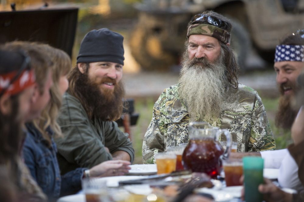 """This undated image released by A&E shows Phil Robertson, flanked by his sons Jase Robertson, left, and Willie Robertson from the popular series """"Duck Dynasty."""" Phil Robertson was suspended for disparaging comments he made to GQ magazine about gay people but was reinstated by the network on Friday, Dec. 27. In a statement Friday, A&E said it decided to bring Robertson back to the reality series after discussions with the Robertson family and """"numerous advocacy groups."""""""