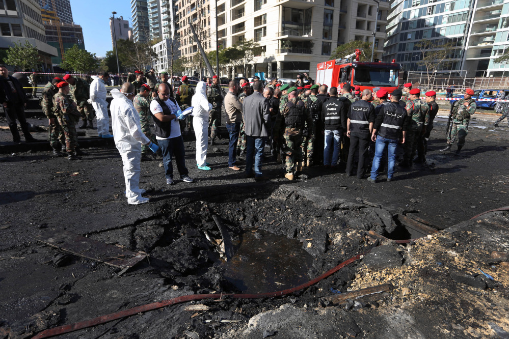 Lebanese army investigators in white coveralls stand next to a blast crater at the scene of an explosion in Beirut, Lebanon, Friday. A powerful car bomb tore through a business district in the center of the Lebanese capital Friday, killing Mohammed Chatah, a prominent pro-Western politician, and at least five other people.
