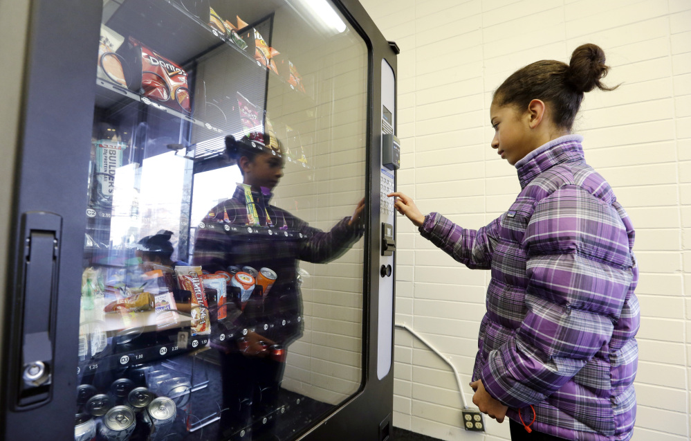 In this Dec. 23, 2013 photo, a 12-year-old girl, who declined to be identified, makes a purchase at a vending machine in Seattle. Office workers in search of snacks will be counting calories along with their change under new labeling regulations for vending machines included in President Barack Obama's health care overhaul law. The Food and Drug Administration, which is expected to release final rules early next year, says requiring calorie information to be displayed on roughly 5 million vending machines nationwide will help consumers make healthier choices.