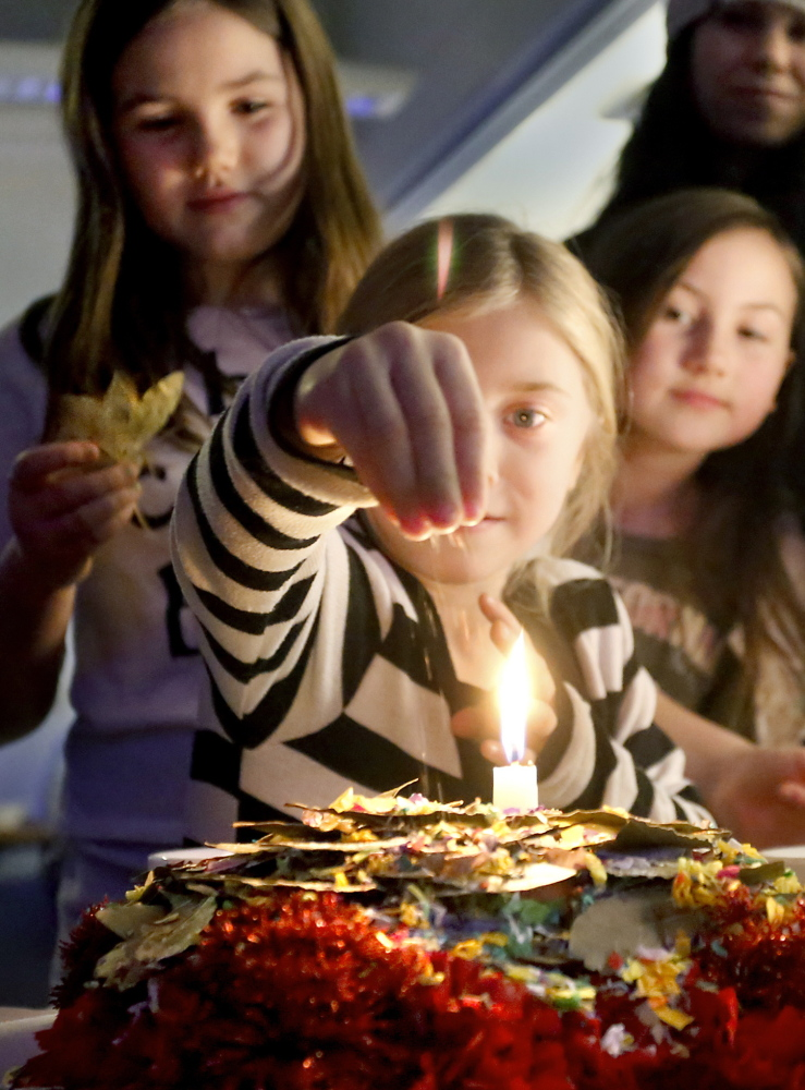 Sugar represents joy, so Bella Martin, 6, of Limerick uses it to sweeten despacho and prayer alike as cousins Brooke Rousey, 11, left, and Lainey Rousey, 8, watch.