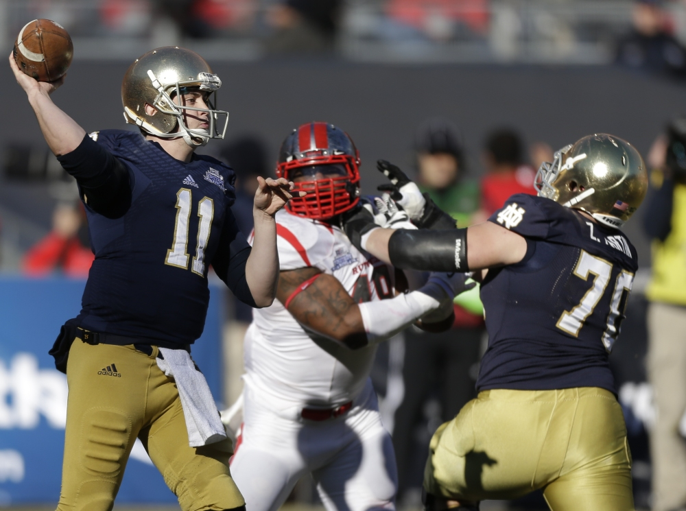 Notre Dame quarterback Tommy Rees throws a pass as lineman Mark Harrell blocks Rutgers' Marcus Thompson in the first half of the Pinstripe Bowl Saturday at Yankee Stadium.