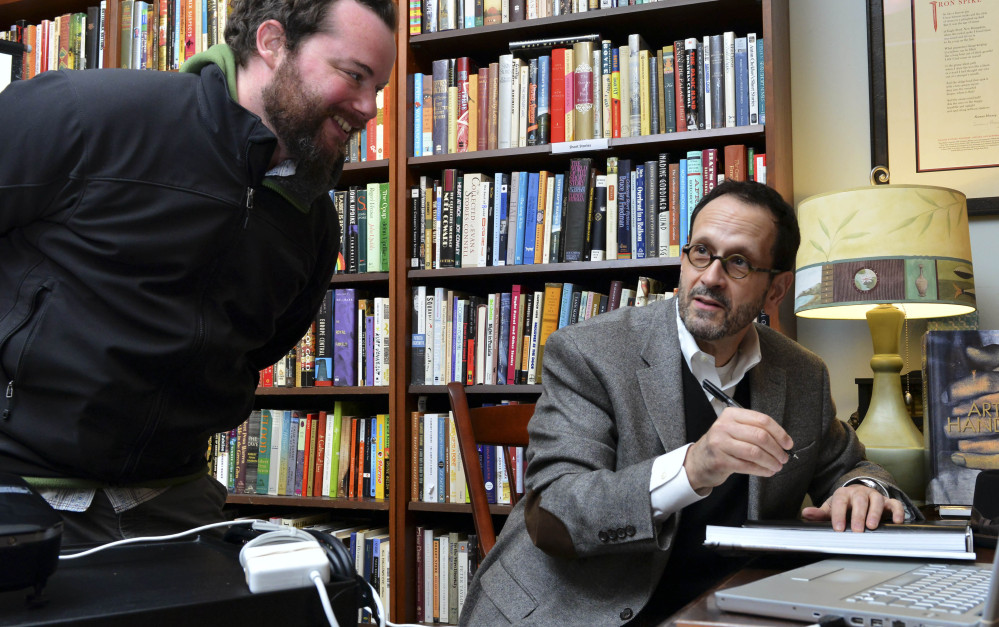 """Photographer Gregory Heisler, right, chats with Paul Murphy as he signs a copy of his first book on his craft, """"Gregory Heisler: 50 Portraits: Stories and Techniques From a Photographer's Photographer,"""" in Easthampton, Mass."""