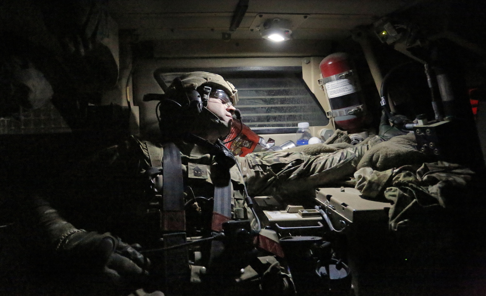 First Sgt. Andrew Pattle of Harrison, sitting in the back of a Mine-Resistant Ambush Protected vehicle, checks on the spacing of vehicles behind his truck as the 41-truck convoy leaves Forward Operating Base Shank with the destination of Bagram Air Field just after midnight on Dec. 24.