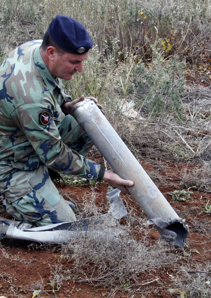 A Lebanese army soldier holds remains of a rocket that struck northern Israel, while inspecting an area in the southern village of Sarada, Lebanon, on Sunday.
