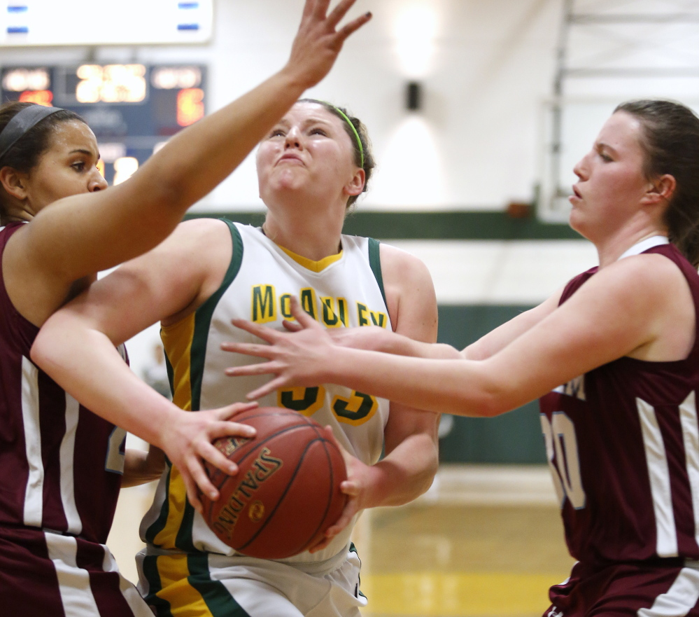 Victoria Lux of McAuley powers her way to the basket between Windham defenders Lonnie Staten, left, and Sadie Nelson on Monday.