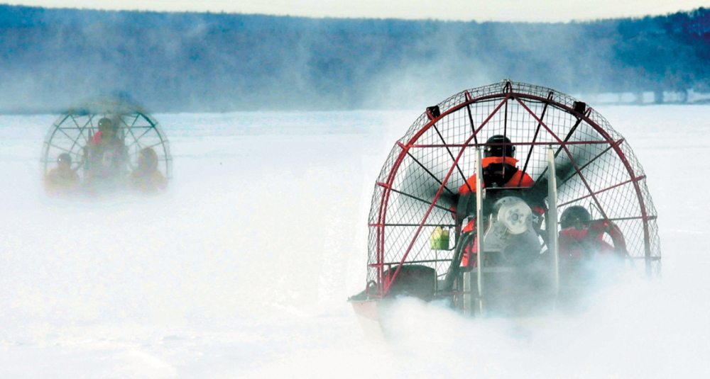 Two Maine Warden Service airboats head out on the ice on Rangeley Lake in Rangeley in early 2013 to the open water location where five snowmobiles went through the ice on Dec. 30, 2012. The warden service and the Maine Snowmobile Association hope that a public service announcement will prod snowmobilers to avoid similar tragedies.