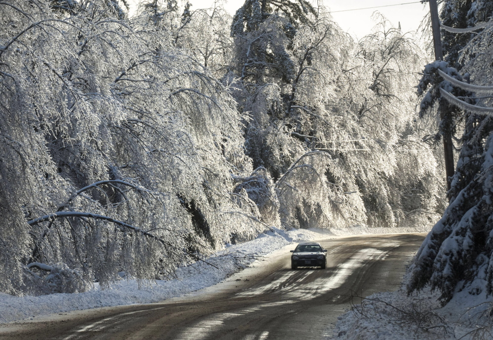 Heavy snow adds to weight of the ice on trees in Hancock County as a car drives along Route 179 in Fletcher's Landing Township northeast of Ellsworth on Monday. Utility companies have not yet tallied the costs of the repairs.