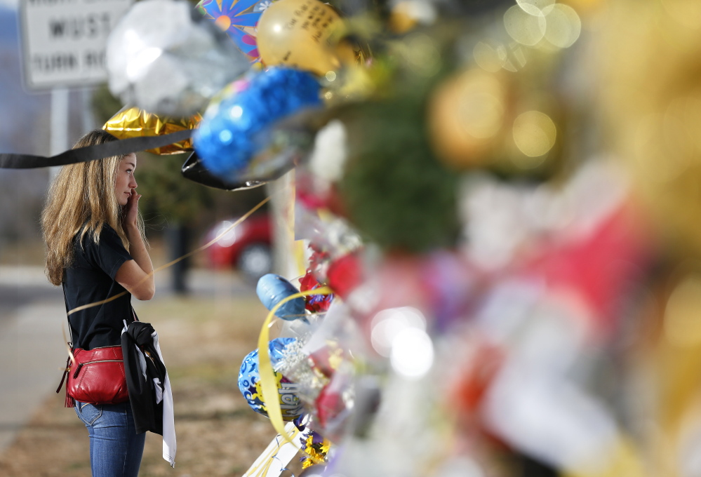 Arapahoe High School student body vice president Grace Marlowe looks at a tribute site for student Claire Davis on Dec. 19, six days after she was shot by a classmate during a school attack, in Centennial, Colo.