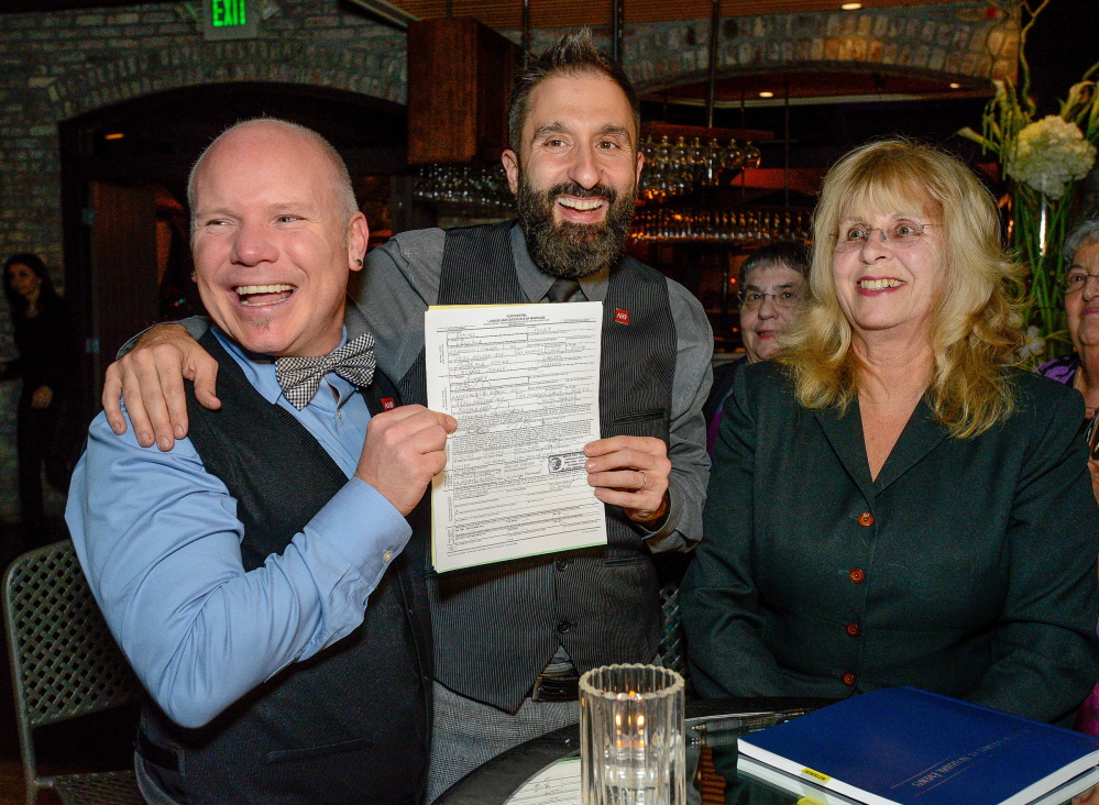 """Aubrey Loots and Danny Leclair show their signed marriage certificate in preparation for their wedding on the AIDS Healthcare Foundation's float """"Living the Dream"""" in the 125th Tournament of Roses Parade in Pasadena, Calif."""