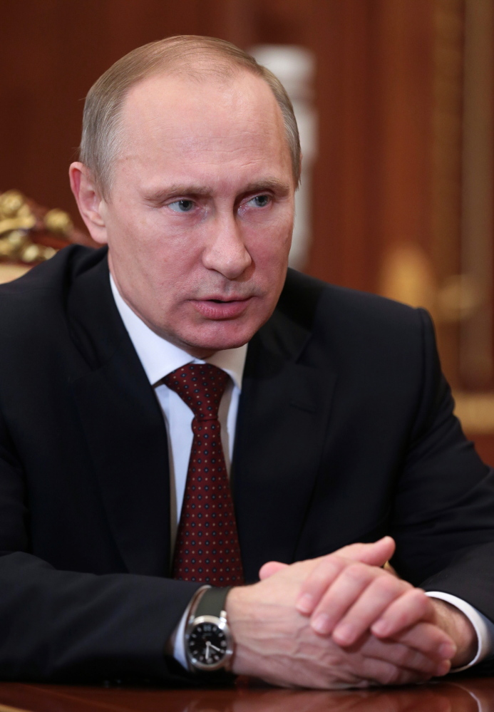 Russian President Vladimir Putin speaks during a meeting with Premier Dmitry Medvedev in Moscow's Kremlin Monday, Dec. 30, 2013. Putin met with officials Monday to discuss the bombings in Volgograd. (AP Photo/RIA Novosti, Mikhail Metzel, Presidential Press Service)