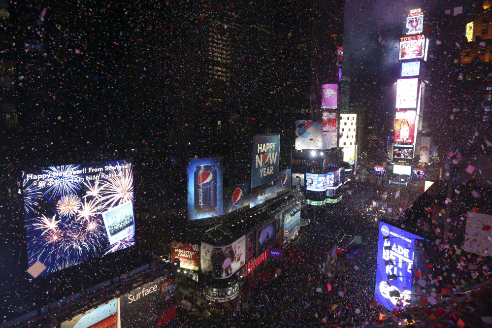 In this Jan. 1, 2013, file photo, donfetti flies over New York's Times Square after the clock strikes midnight during the New Year's Eve celebration as seen from the Marriott Marquis hotel in New York.