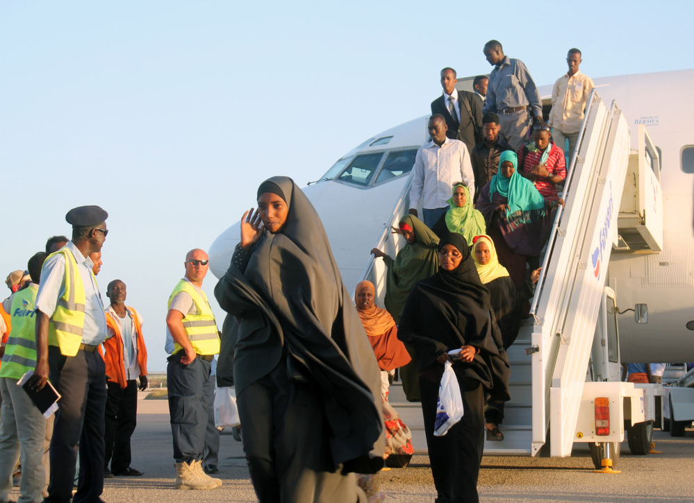 Somali who fled from South Sudan's fighting get off a plane at Mogadishu's International airport, Monday, Dec, 30, 2013. The Somali government has evacuated up to 150 Somalis who escaped from the fighting between South Sudanese government troops and rebel fighters.