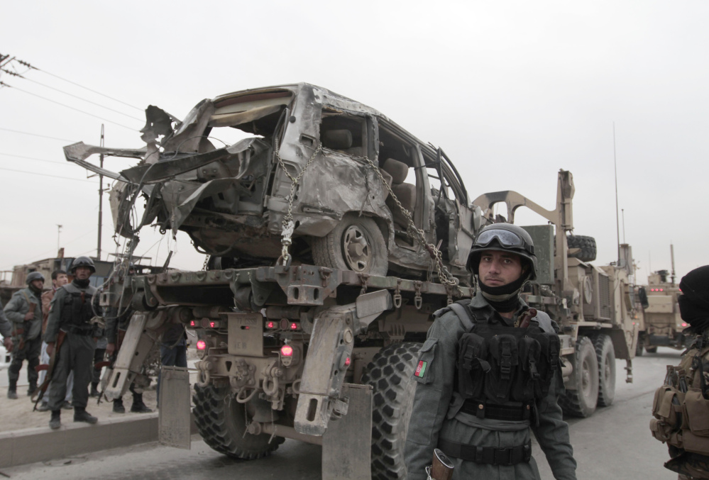 A U.S. military wrecker carries away a vehicle that was destroyed in a suicide car bomb attack on the Jalalabad-Kabul road in Kabul, Afghanistan, on Friday. The U.S.-led coalition in Afghanistan says several service members were killed when a suicide car bomber attacked their convoy in an eastern district of the capital, Kabul.