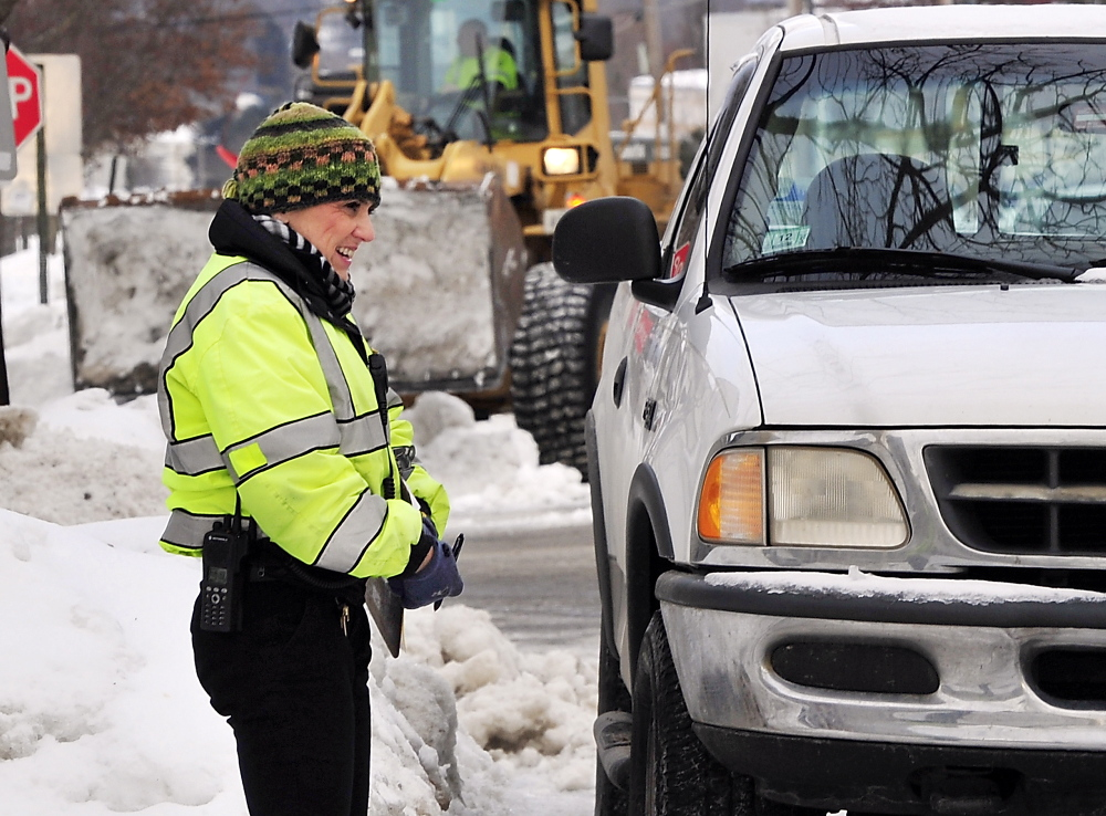 "Dressed for the cold weather, Ann Rand, parking control officer for Portland, coordinates the towing of a truck parked in a city services tow zone on North Street as crews atempt to remove snow from the last two storms. Her comment: ""It's cold!"""