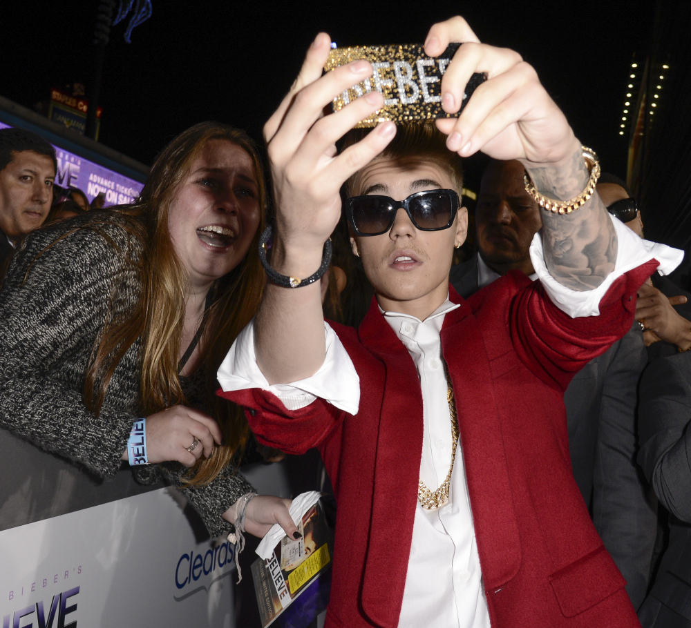 """Singer Justin Bieber takes a """"selfie"""" with a fan at the premiere of the feature film """"Justin Bieber's Believe"""" at Regal Cinemas L.A. Live in Los Angeles. The word selfie is on a list of among those words selected for elimination in Michigan's Lake Superior State University's 39th annual batch of words to banish due to overuse, overreliance and overall fatigue."""