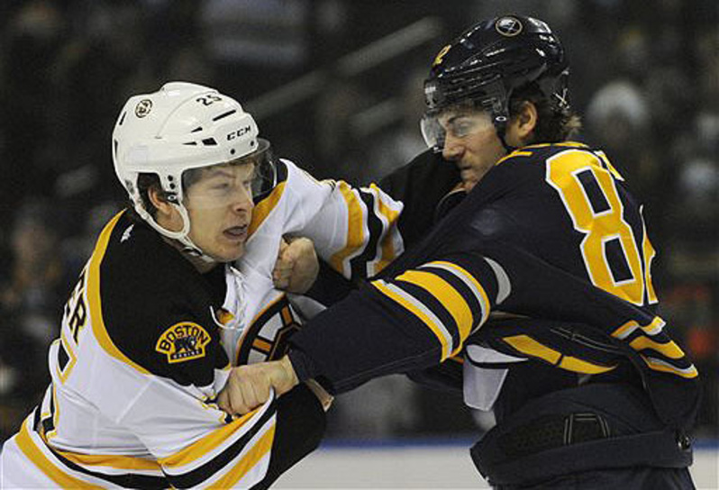 Boston Bruins' Nick Fraser (25) gets locked up with Buffalo Sabres' Marcus Foligno (82) during a fight in the first period in Buffalo, N.Y., Thursday. Buffalo won 4-2.