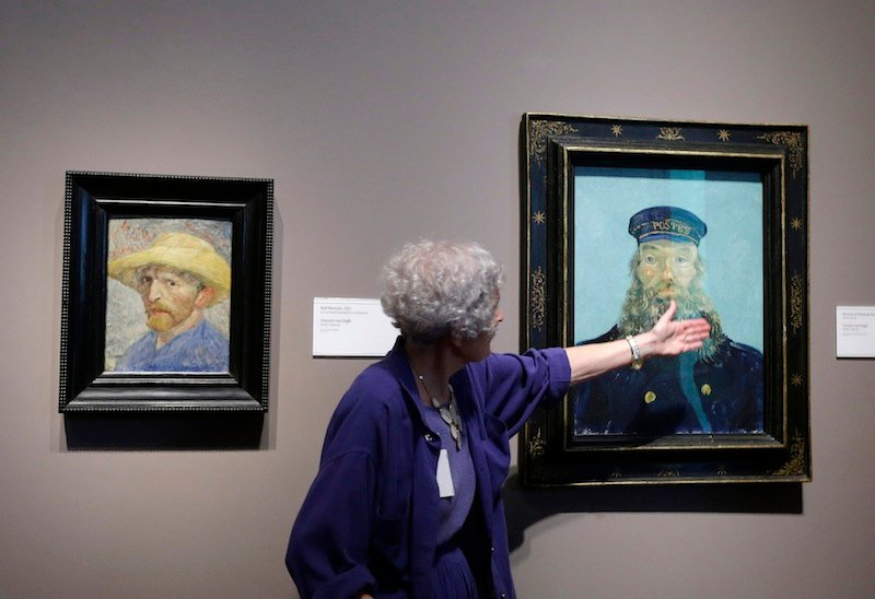 In a June 13, 2013 file photo, Detroit Institute of Arts docent Lea Schelke points out details in the Portrait of Postman Roulin by Van Gogh displayed at the museum in Detroit. A closer look at the DIA art collection now being appraised by Christie's. It's report to state-appointed emergency manager Kevyn Orr could come out by mid-December. It's looking more and more like that's what debtors want to go after.