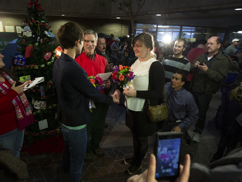 In this Friday, Dec. 20, 2013, file photo, Natalie Dicou, left, and Nicole Christensen, right, are married by Salt Lake City Mayor Ralph Becker, middle, in the lobby of the Salt Lake County Clerk's Office in Salt Lake City. Utah asked the U.S. Supreme Court on Tuesday, Dec. 31, 2013, for an emergency stay on more than 900 marriage licenses issued to gay couples since Dec. 20.