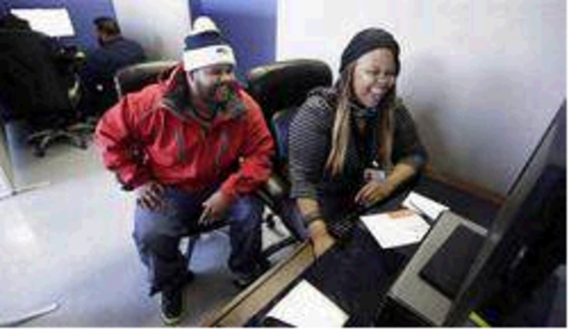 Kenya Williams helps unemployed construction worker Jerome Davis Jr., 36, sign up for Medicaid under expanded eligibility rules in Chicago on Nov. 8. Maine would be better off accepting federal funds to expand MaineCare than spending $1 million to review DHHS programs, a reader says.