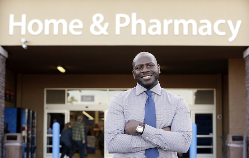 James Lott stands outside the Walmart store where he works as a pharmacist in Bonney Lake, Wash. Lott, who lives in Renton, Wash., a suburb of Seattle, adds significantly to his six-figure job salary by day-trading stocks.