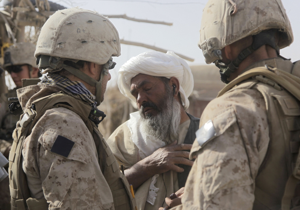 U.S. Marine Lt. Raymond Mahoney, right, and an interpreter speak to a man in the village of Dahaneh, Afghanistan, in 2009. Congress has allocated more than 8,700 special imigrant visas for Afghans who are facing persecution because of their assistance to the U.S. But as of November, the U.S. government has approved fewer than 1,700 of them, with a backlog of some 5,000.