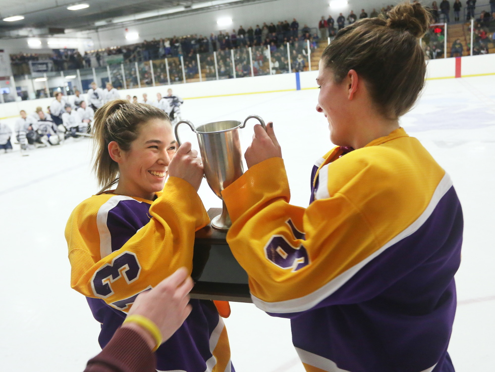 Jill Hannigan, left, and Katie Randall of Cheverus accept the trophy, Wednesday, Jan. 1, 2014, after defeating Portland to win the City Cup hockey game at Portland Ice Arena.