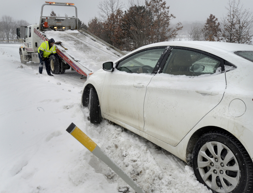 AAA tow truck driver Matt Ivey has a busy day with disabled cars like this one that had to be pulled from a snowbank on the off ramp of Exit 5B southbound on I-295 in Portland on Thursday.