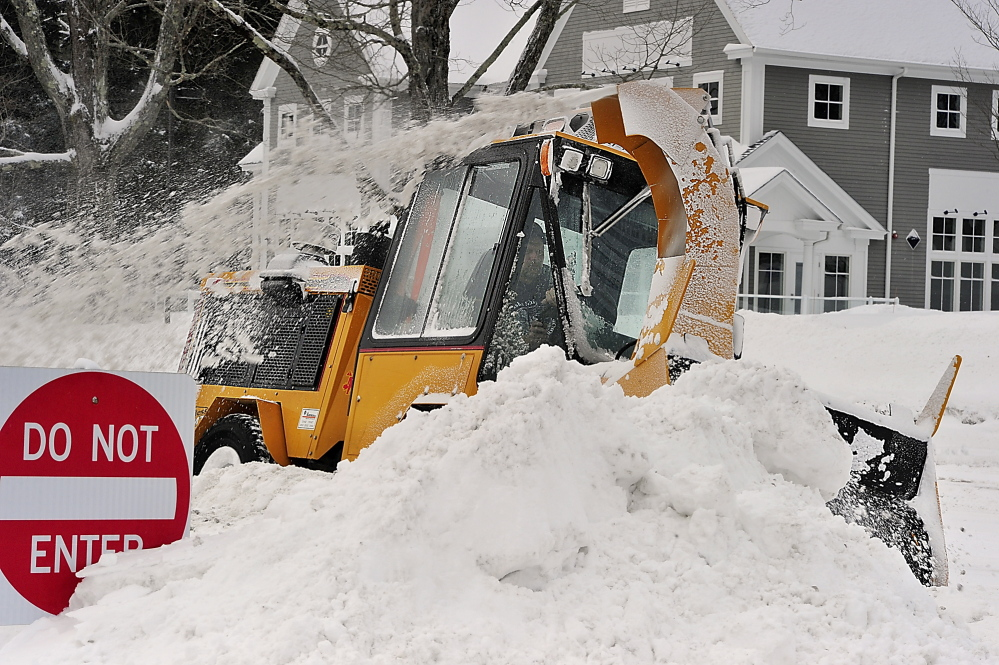 Eric Gibson, an employee of Freeport Public Works, grinds through some pretty deep snow drifts Friday as he cleans the sidewalk in Freeport near Bath Savings Bank. Gordon Chibroski, Staff Photographer