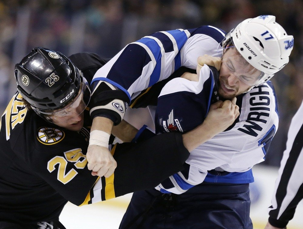 Matt Fraser of the Bruins battles with Winnipeg's James Wright – one of two fights in the opening four minutes Saturday afternoon. Boston won, 4-1.