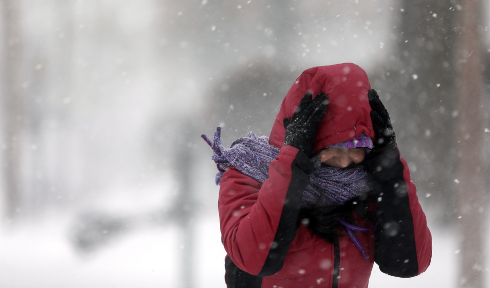 Srirupa Chatterjee holds her hood as she crosses a street in St. Louis on Sunday. Heavy snow continued to fall Sunday, with forecasters calling for up to a foot in eastern Missouri and parts of central Illinois followed by bitter cold.
