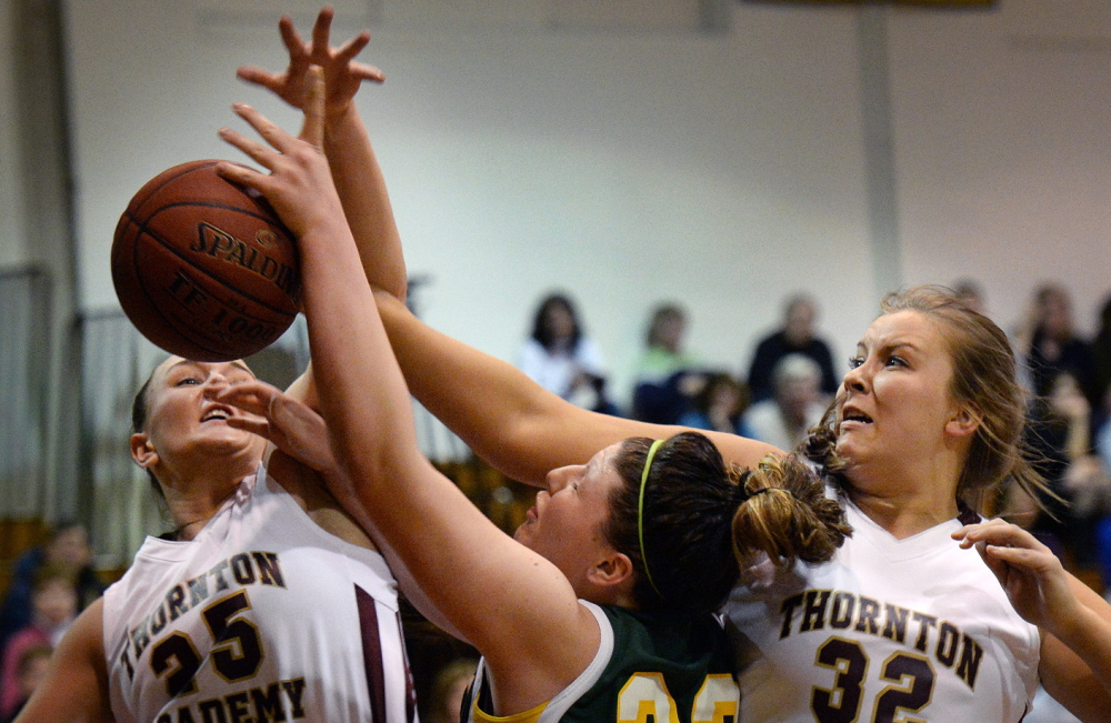 Victoria Lux of McAuley, center, finds rough going Tuesday night as she attempts to drive against Olivia Shaw, left, and Lauren Leskowsky of Thornton Academy during Thornton's 50-49 come-from-behind victory that put an end to McAuley's 56-game win streak.