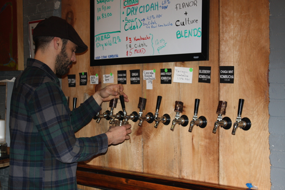 Eli Cayer, founder of the Urban Farm Fermentory on Anderson Street in Portland, pours a kombucha sample during a winter market.