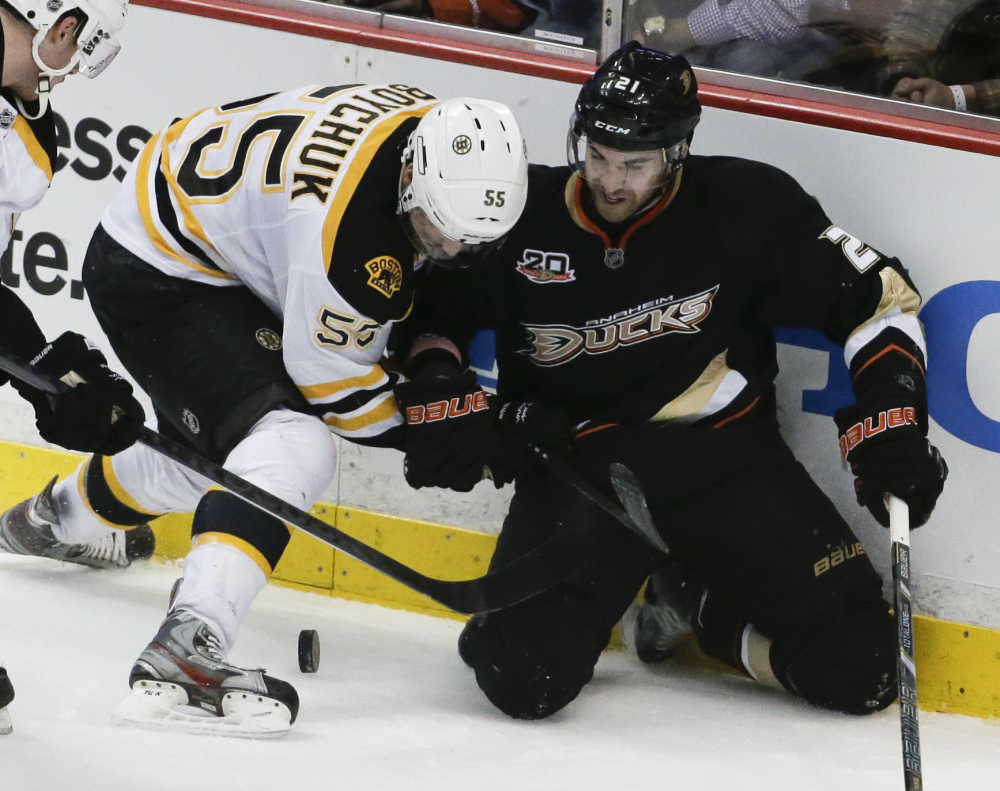 Boston Bruins defenseman Johnny Boychuk, left, battles Anaheim Ducks right wing Kyle Palmieri for the puck during the second period Tuesday in Anaheim, Calif.