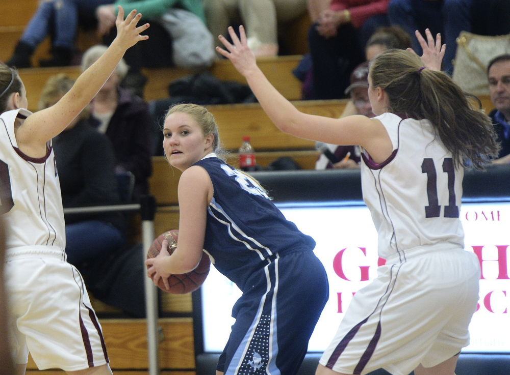 Emma Riley of Westbrook looks for an open teammate while guarded by Gorham's Jessica Rexrode, left, and Caitlyn Hawxswell during an SMAA game Friday night in Gorham. Gorham won, 58-37.