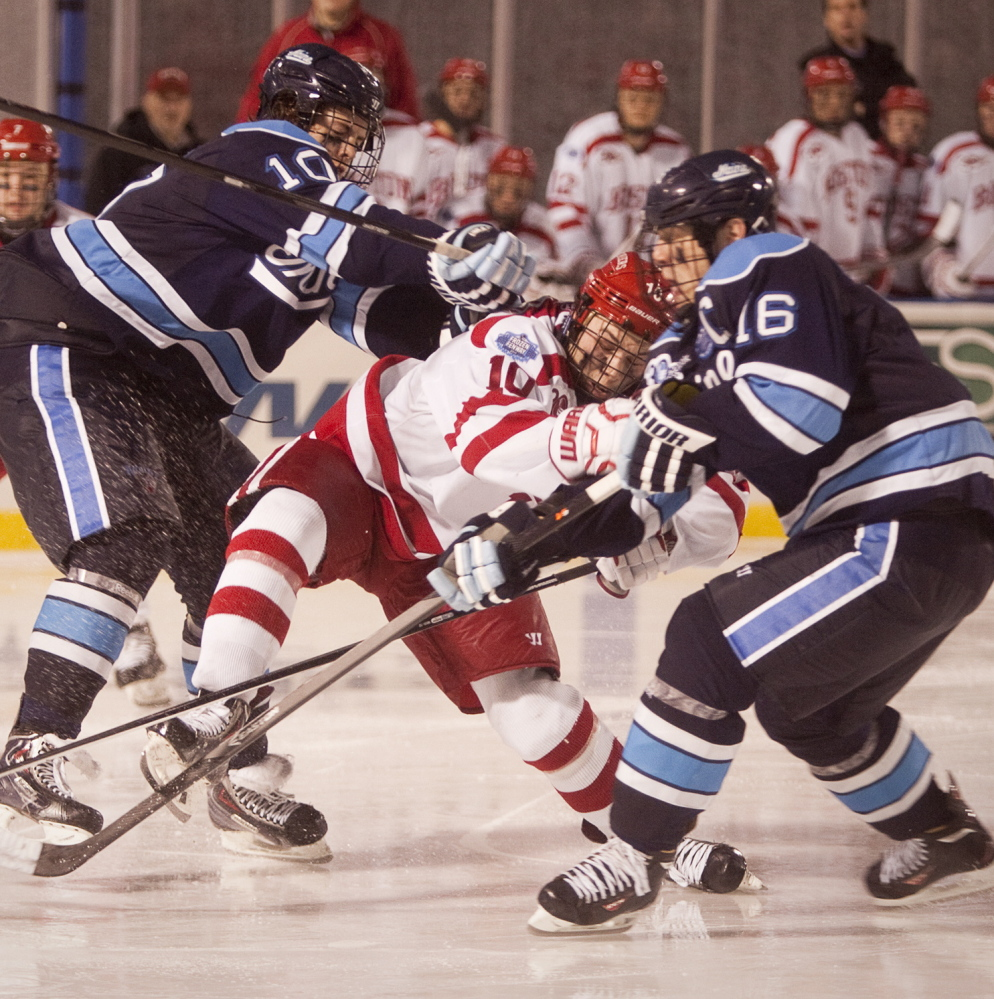 UMaine players Ben Hutton, left, and Brice O'Connor team up on Boston University's Danny O'Regan during first period on Saturday.