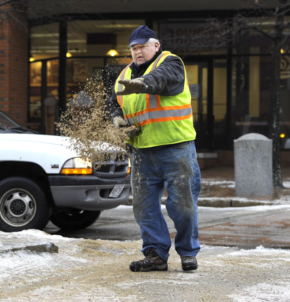 Dennis Lamb with Portland's Downtown District spreads sand on walkways at Free and Temple streets Saturday as freezing rain coated sidewalks and streets with ice.