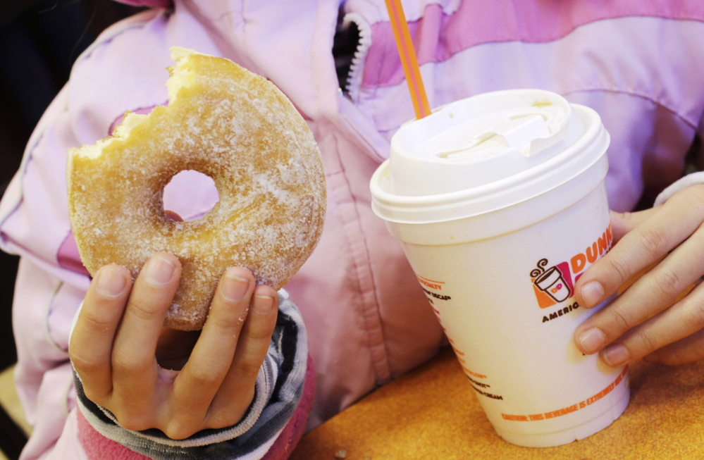 FILE - In this Feb. 14, 2013 file photo, a girl holds a beverage, served in a foam cup, and a donut at a Dunkin' Donuts in New York. Takeout-craving New York City is pondering whether to outlaw plastic foam to-go cups and trays, unless a yearlong inquiry shows they can be recycled effectively. (AP Photo/Mark Lennihan, File)