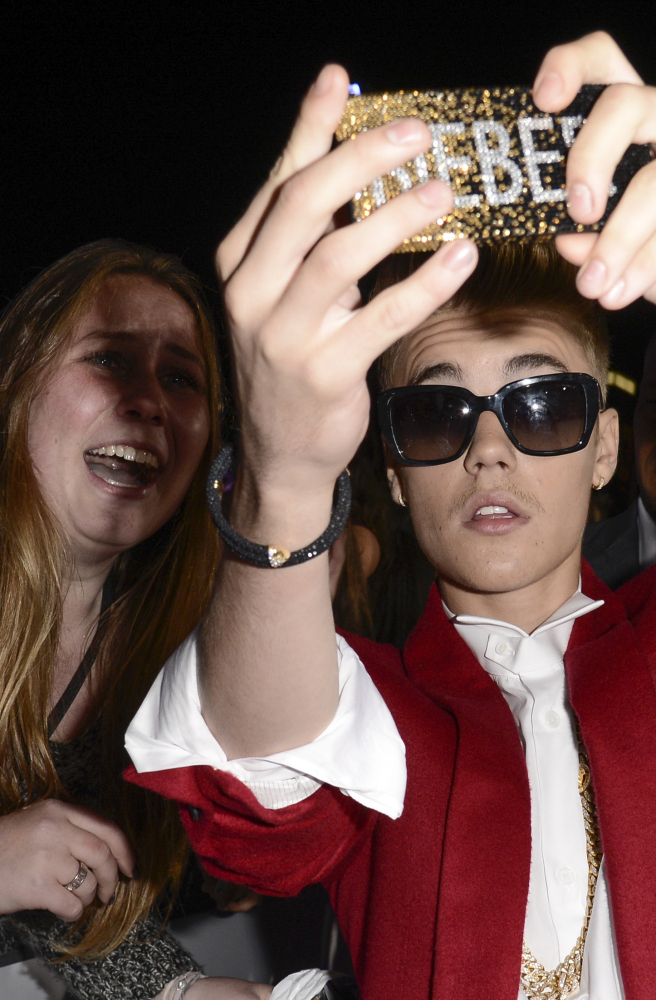 Justin Bieber takes a selfie with a fan in Los Angeles. A member of his entourage was arrested after police found cocaine in plain view in Bieber's home Tuesday.