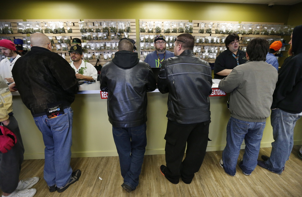 Employees help customers at the crowded sales counter at the Medicine Man marijuana retail store in Denver this month. A group of marijuana activists want another pot vote in Colorado, to loosen restrictions on who can have it.