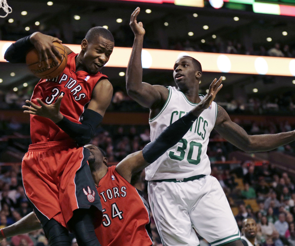 Terrence Ross of the Toronto Raptors hauls down a rebound Wednesday night in front of Brandon Bass of the Boston Celtics in the first quarter of Boston's 88-83 victory. Boston snapped a nine-game losing streak.