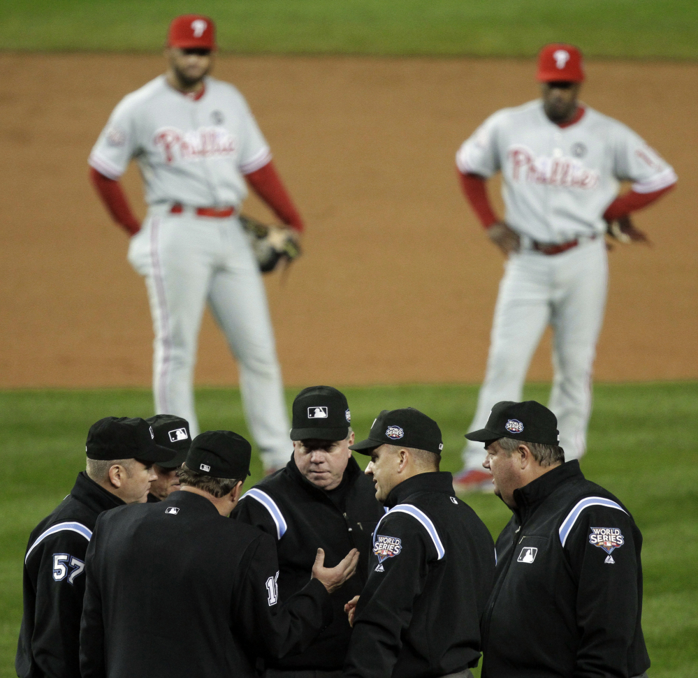 AP Photo/Julie Jacobson In this Oct. 28, 2009, file photo, Philadelphia Phillies' Pedro Feliz, left, and Jimmy Rollins watch in the background, as umpires discuss a call at first base during the Game 1 of the World Series. Major League Baseball announced Thursday, Jan. 16, 2014, that it will greatly expand instant replay to review close calls starting this season.